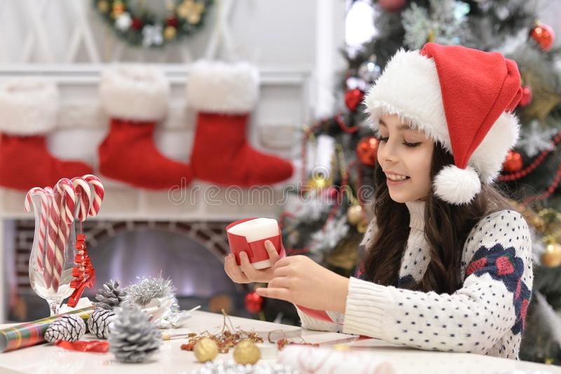 Happy girl in Santa hat prapring for Christmas sitting at the table and holding Christmas decoration royalty free stock images