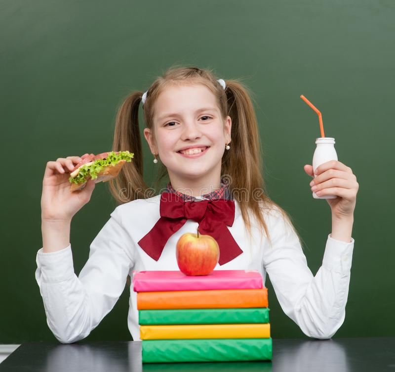 Happy girl with school food near empty green chalkboard royalty free stock images