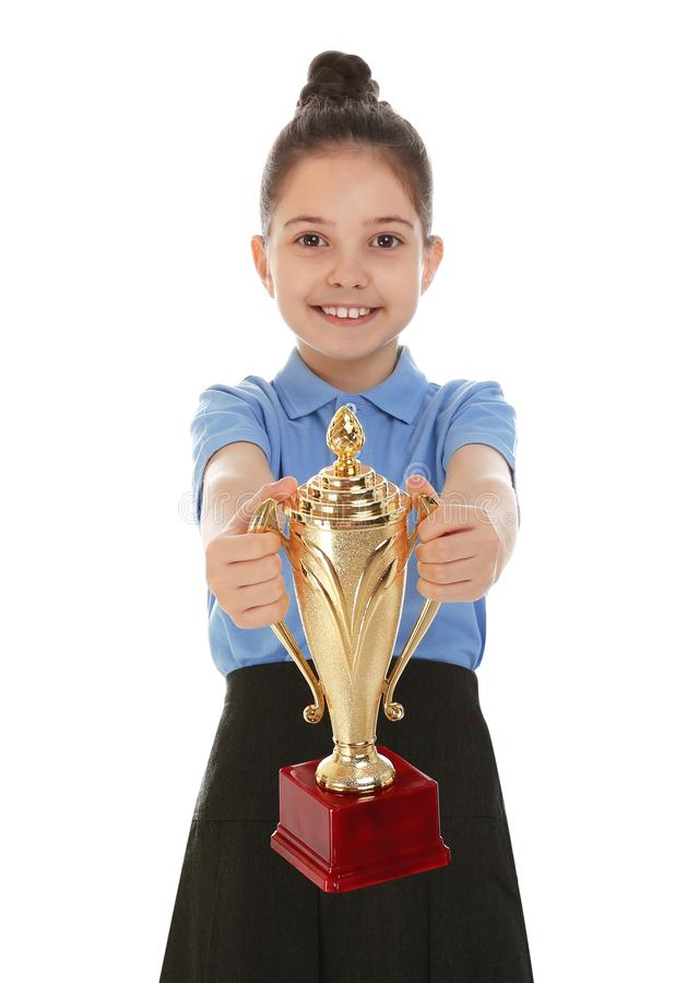 Happy girl in school uniform with golden winning cup isolated. On white royalty free stock photography