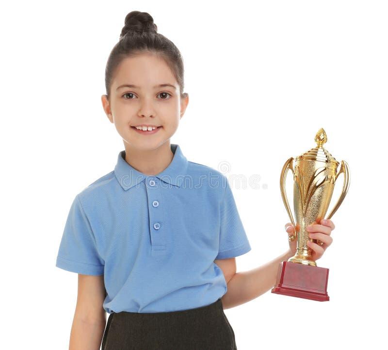 Happy girl in school uniform with golden winning cup on white. Happy girl in school uniform with golden winning cup isolated on white stock images
