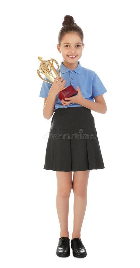 Happy girl in school uniform with golden winning cup on white. Happy girl in school uniform with golden winning cup isolated on white stock photo