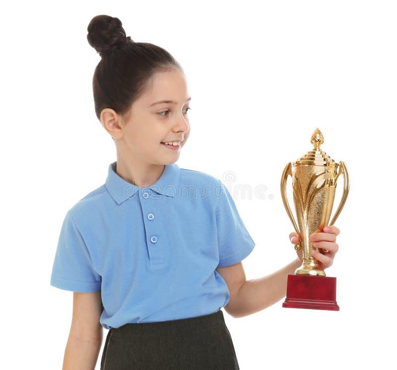 Happy girl in school uniform with golden winning cup on white. Happy girl in school uniform with golden winning cup isolated on white stock image