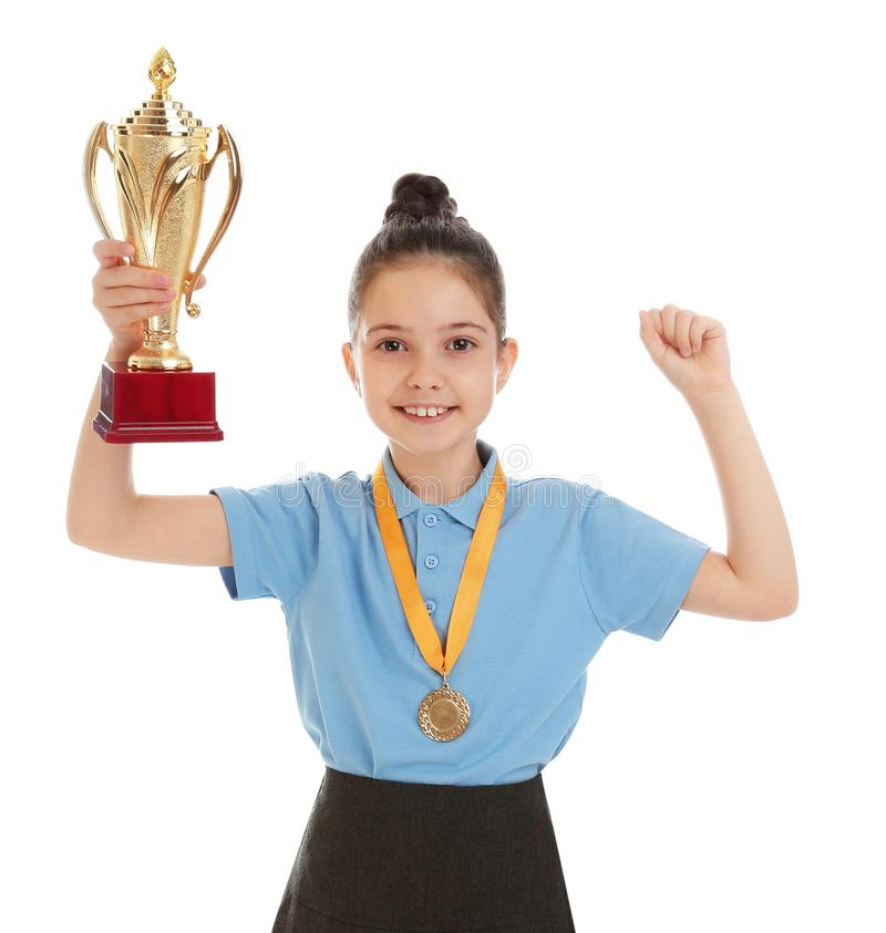 Happy girl in school uniform with golden winning cup and medal on white. Happy girl in school uniform with golden winning cup and medal isolated on white royalty free stock image