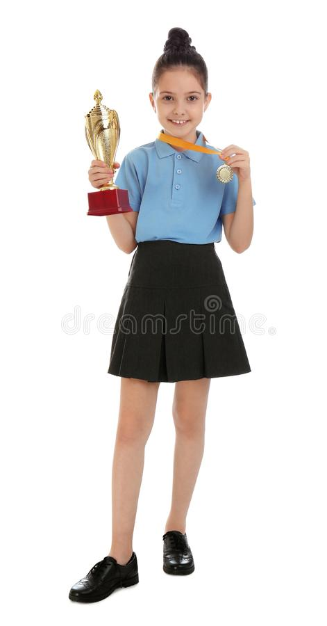 Happy girl in school uniform with golden winning cup and medal on white. Happy girl in school uniform with golden winning cup and medal isolated on white royalty free stock photos