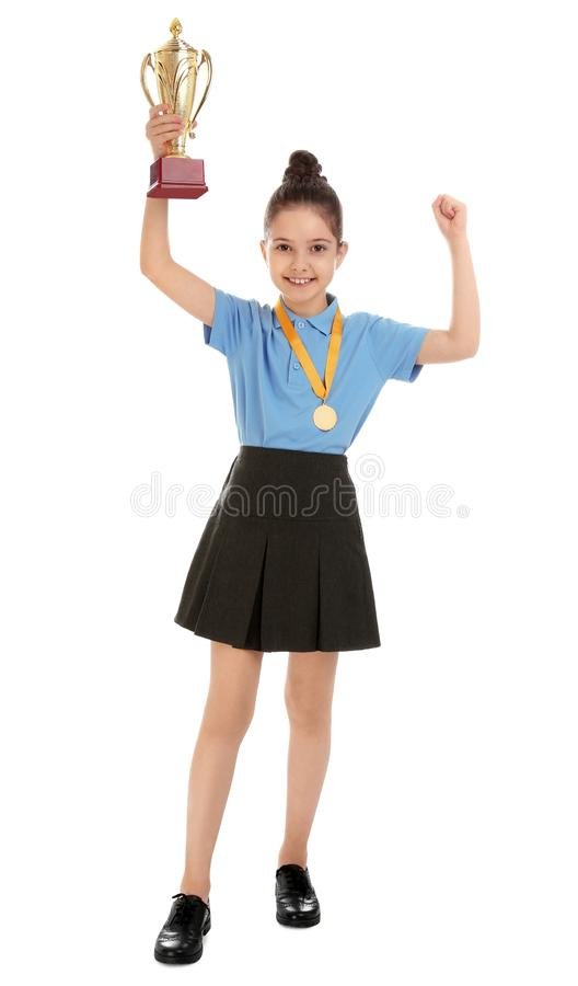 Happy girl in school uniform with golden winning cup and medal on white. Happy girl in school uniform with golden winning cup and medal isolated on white stock photography