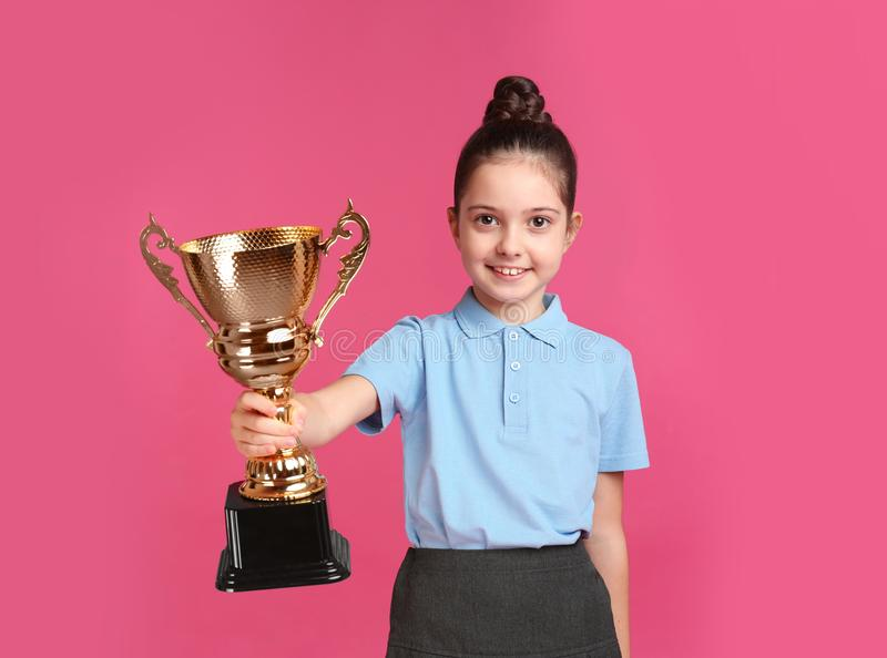 Happy girl in school uniform with golden winning cup on pink background. Space for text stock image