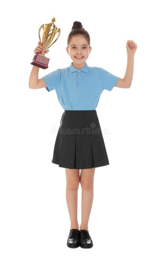 Happy girl in school uniform with golden winning cup on white. Happy girl in school uniform with golden winning cup isolated on white royalty free stock images