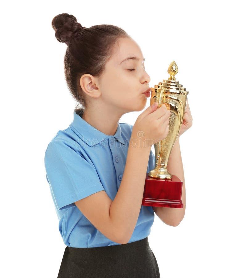 Happy girl in school uniform kissing golden winning cup on white. Happy girl in school uniform kissing golden winning cup isolated on white stock photos