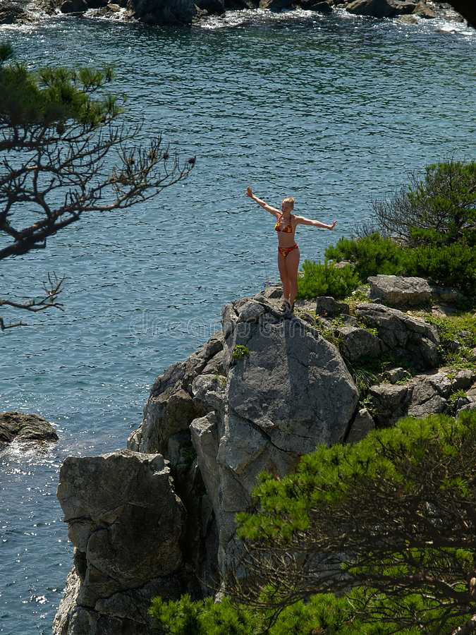 Happy girl on the seaside rock stock image