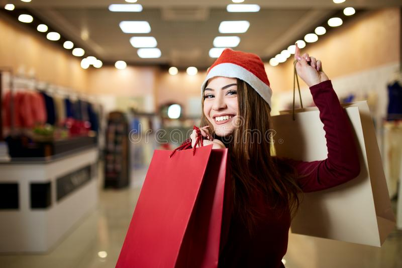 Happy girl shopping gifts in mall on christmas sale. New year holidays shopping idea concept. Smiling pretty caucasian. Happy girl shopping gifts in mall on stock photo