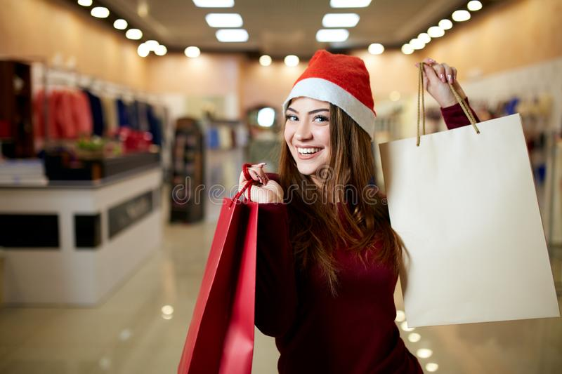 Happy girl shopping gifts in mall on christmas sale. New year holidays shopping idea concept. Smiling pretty caucasian. Happy girl shopping gifts in mall on stock photos