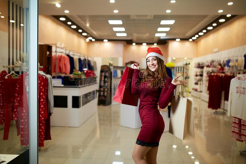 Happy girl shopping gifts in mall on christmas sale. New year holidays shopping idea concept. Smiling pretty caucasian. Happy girl shopping gifts in mall on royalty free stock image