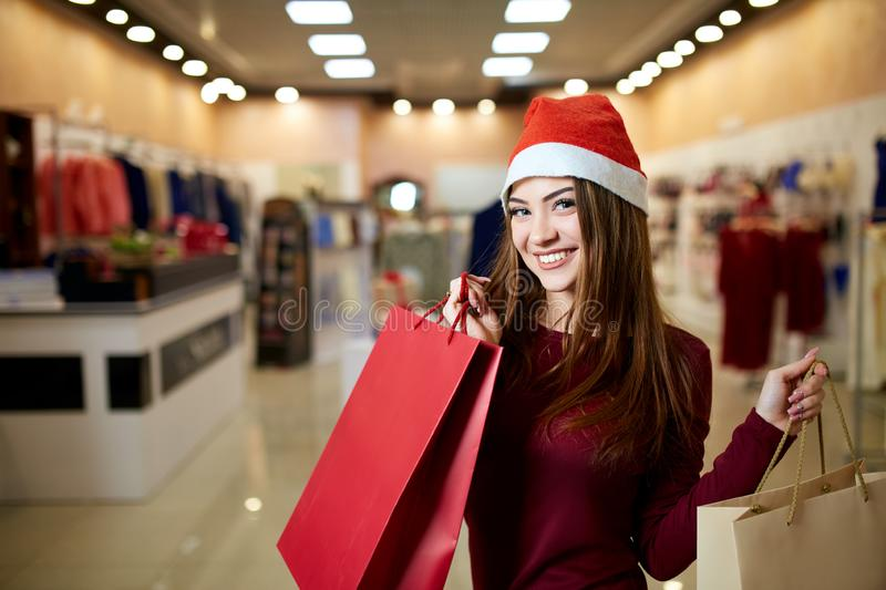 Happy girl shopping gifts in mall on christmas sale. New year holidays shopping idea concept. Smiling pretty caucasian. Happy girl shopping gifts in mall on stock photography