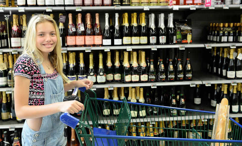 Happy girl with shopping trolley. Bottles of alcohol on supermarket shelves in background royalty free stock images
