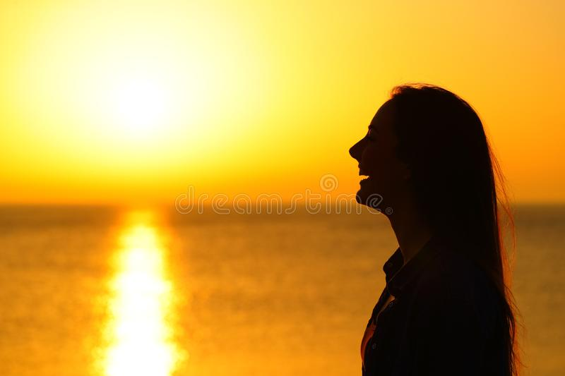 Happy girl silhouette contemplating sun at sunset royalty free stock photography