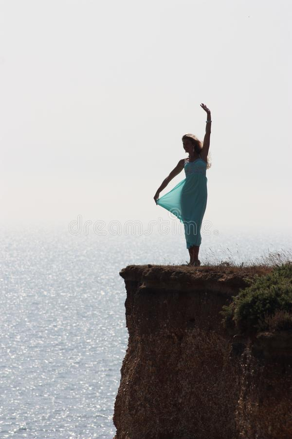 Happy girl silhouette standing outdoor on edge cliff sea shore stock images