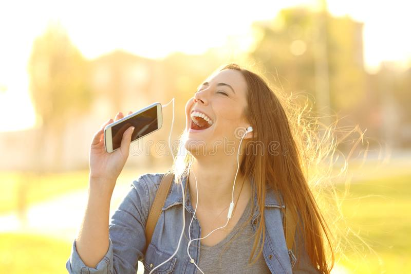 Happy girl singing listening to music at sunset stock photography