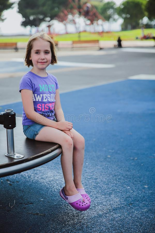 Happy girl sits on the children's playground on the carousel. royalty free stock photography