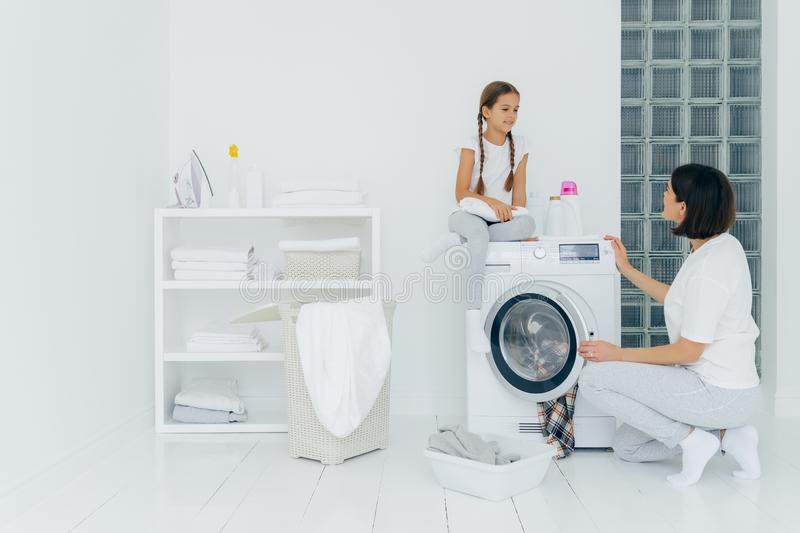 Happy girl sits at washing machine, has pleasant conversation with mother, being in laundry room, woman loads washer with dirty. Happy girl sits at washing stock photo