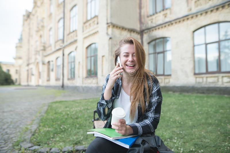Happy girl sitting on a bench with books and coffee, talking on the phone and laughing stock photography