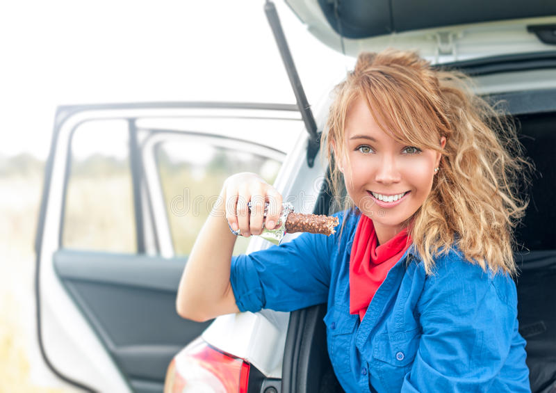 Happy girl sitting in car and holding chocolate. stock photography