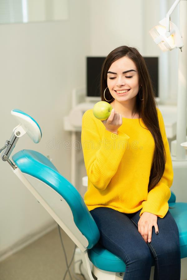 Happy girl sitting in dental chair and showing fresh apples after successful dental treatment stock photo