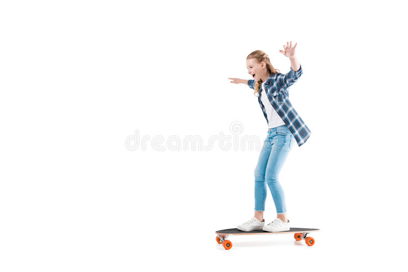 Happy girl with skateboard isolated on white in studio. Adorable happy girl with skateboard isolated on white in studio stock photo