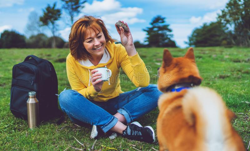 Happy girl with smile drink cup playing with red japanese dog shiba inu on green grass in the outdoors nature park stock photo