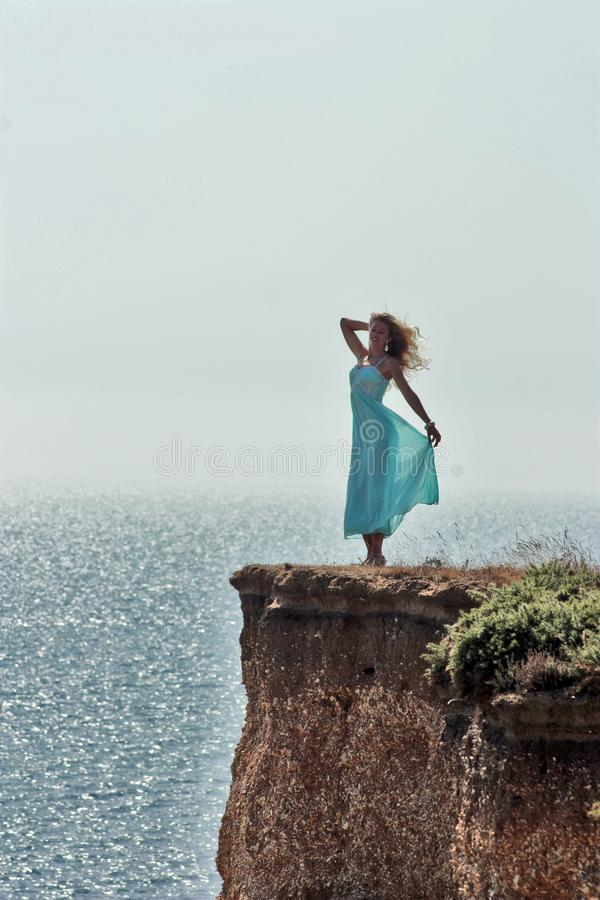 Happy girl in blue dress standing on edge cliff royalty free stock photos