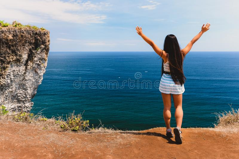Happy girl standing with raised hands on the top of mountain cliff on background amazing nature landscape tropical island Bali, In stock images