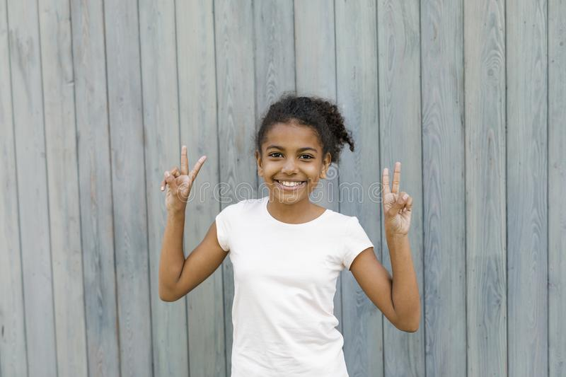 Happy girl standing at wall outdoors royalty free stock photo