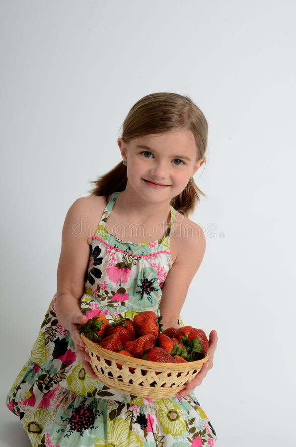 Happy girl with strawberries stock photo