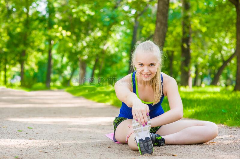 Happy girl stretching legs before run royalty free stock image