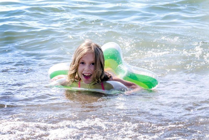 Happy girl swimming with a star float toy stock photos