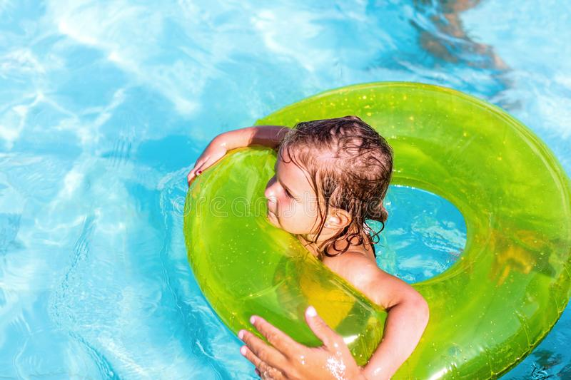 .Happy girl swims in a pool in at green life preserver stock image