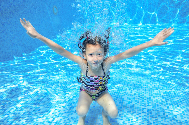 Happy girl swims in pool underwater, active kid swimming and having fun royalty free stock image