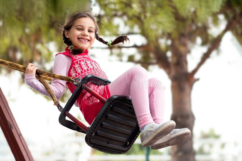 Happy Girl Swinging At Playground Outdoors royalty free stock image