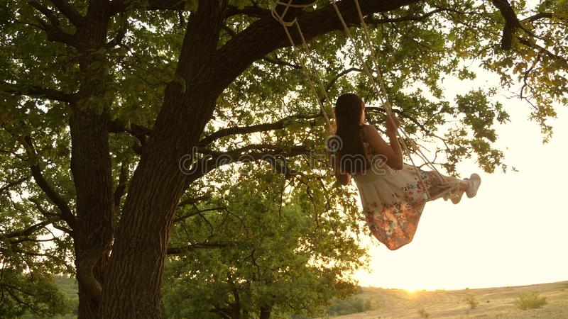Happy girl swinging on a rope swing on an oak branch. young girl in a white dress in the park. teen girl enjoys a flight. Happy girl swinging on rope swing on an royalty free stock photos