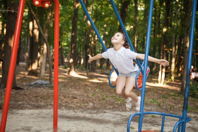 Happy girl swinging on a swing stock photography