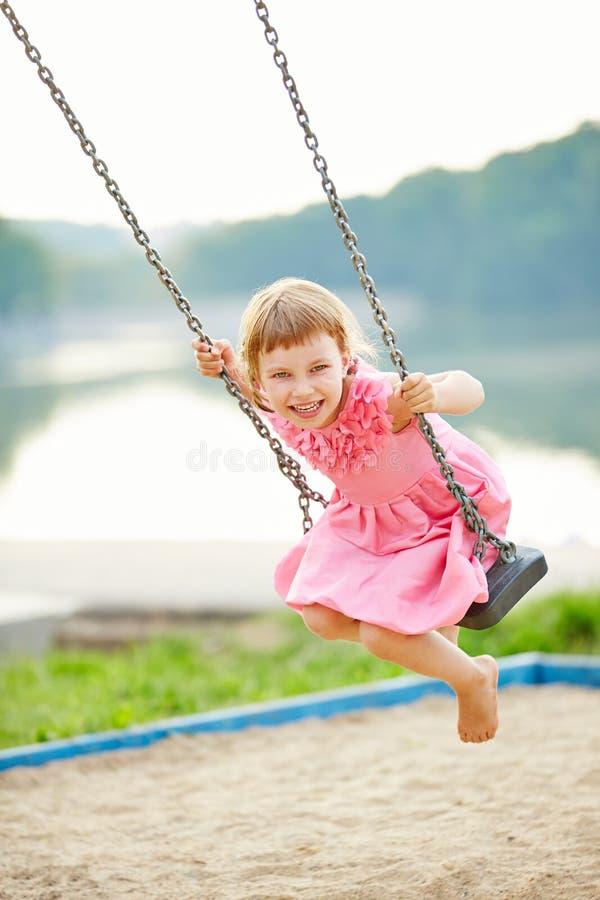 Happy girl swinging on swing royalty free stock photos
