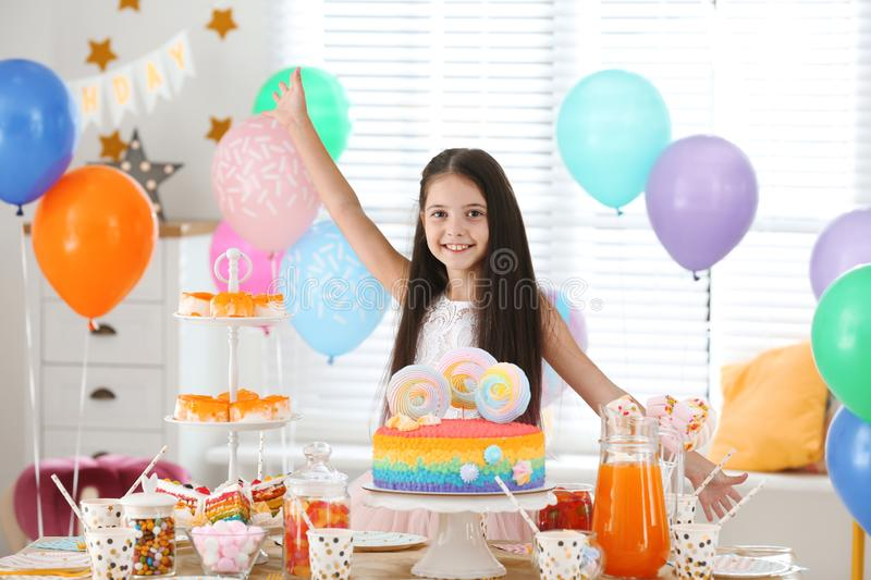Happy girl at table with treats in room decorated for party stock photography