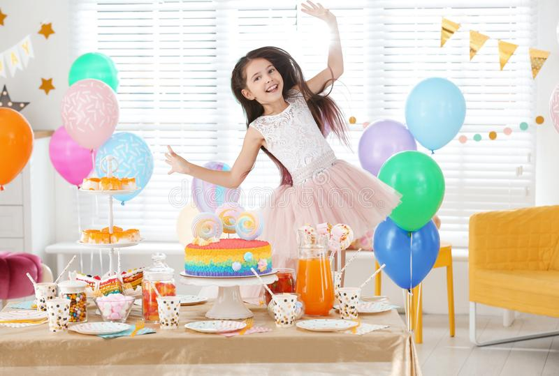 Happy girl at table with treats in room decorated for party stock images