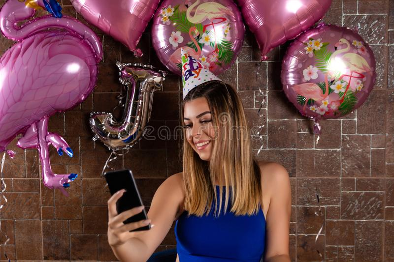 Happy girl taking a selfie and celebrating a birthday with a cap on head. Happy cute and beautiful girl taking a selfie and celebrating a birthday with a cap on royalty free stock photo