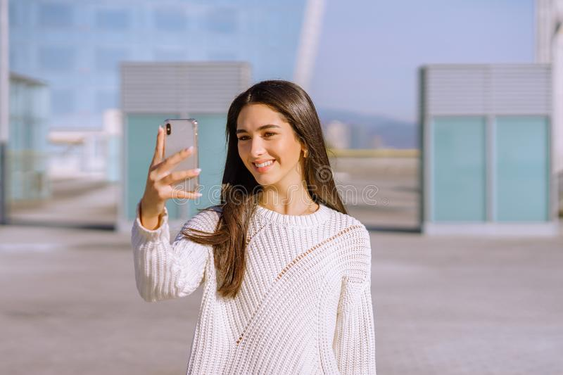 Happy girl taking a selfie photo with white sweater in urban city background - image. Happy girl taking a selfie photo in urban city background - image stock photography