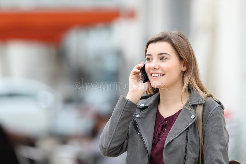 Happy girl talking on mobile phone walking in the street royalty free stock photos