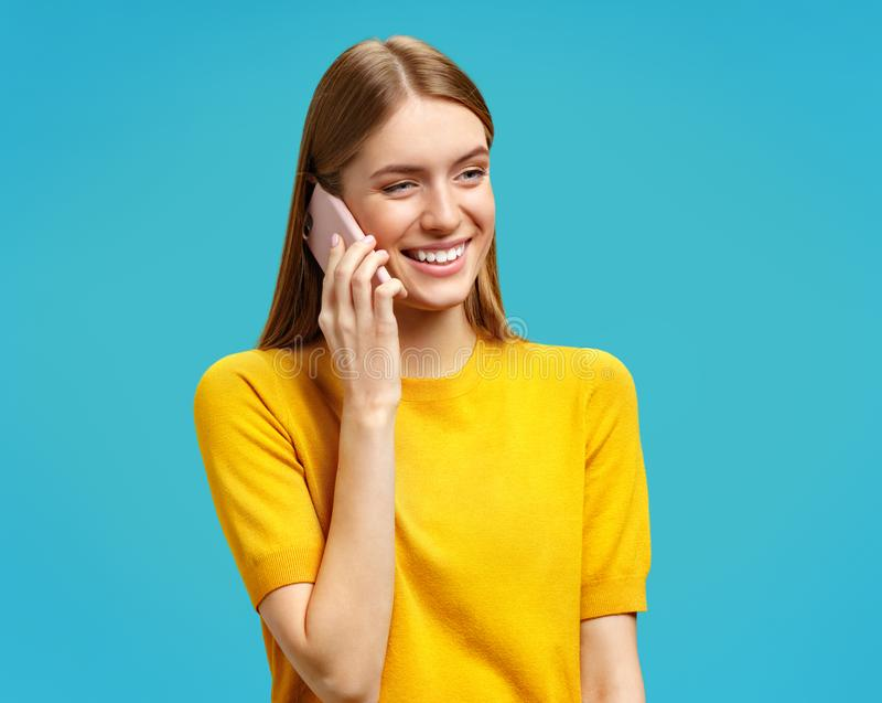 Happy girl talks on phone with positive expression. Photo of attractive girl in yellow sweater on blue background stock photos