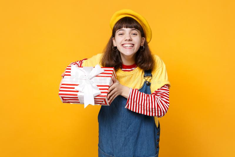 Happy girl teenager in french beret, denim sundress holding red striped present box with gift ribbon isolated on yellow royalty free stock photography