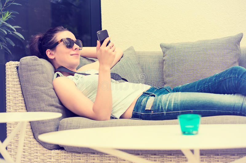 Happy girl texting on the smart phone in a hotel restaurant terrace lounge stock images