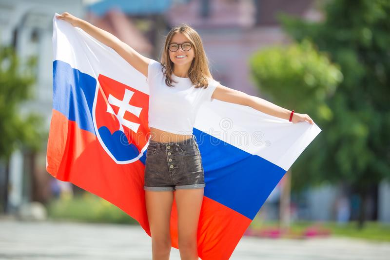 Happy girl tourist walking in the street with flag of slovak republic. Woman, slovakia, national, caucasian, young, female, beautiful, slovakian, people stock image