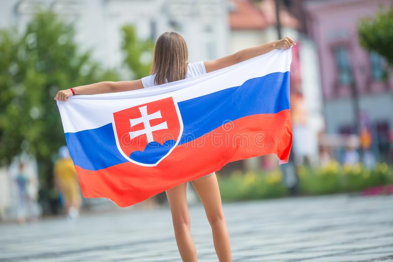 Happy girl tourist walking in the street with flag of slovak republic. Woman, slovakia, national, caucasian, young, female, beautiful, slovakian, people stock images